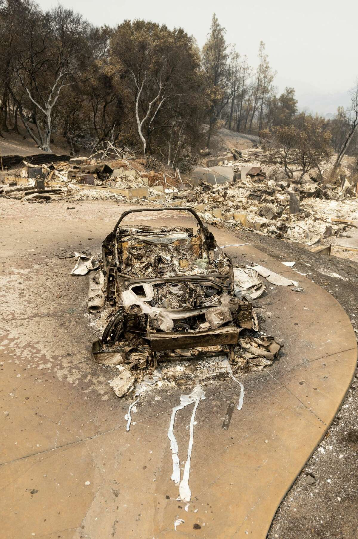 A scorched vehicle rests in a driveway following the LNU Lightning Complex fires in Napa County, Calif. on Monday, Aug. 24, 2020.