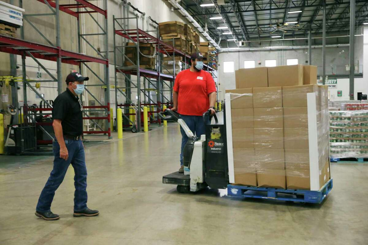 San Antonio Food Bank Warehouse Manager David Carvajal, left, and Victor Mariscal receive the first five pallets of produce from the CRE8AD8/USDA contract, Thursday, May 28, 2020.