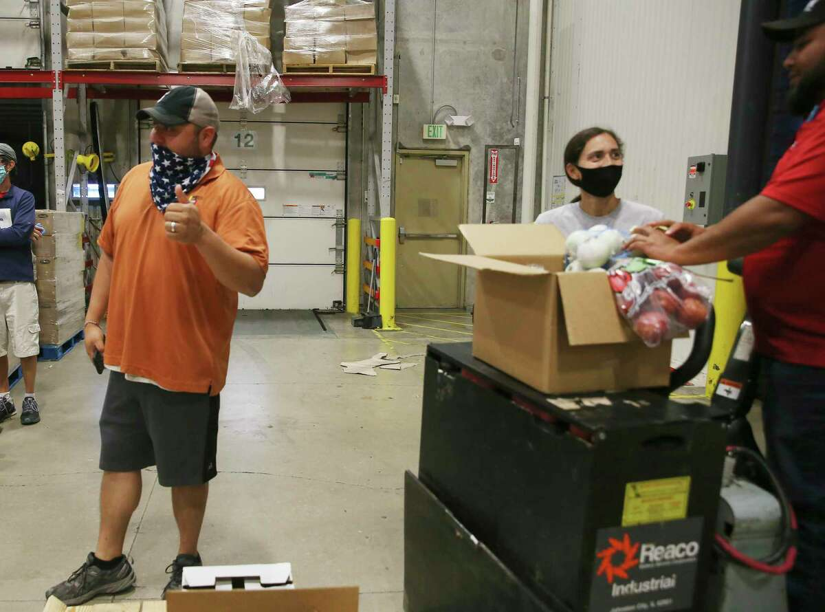 CRE8AD8 owner Gregorio Palomino poses by a box of produce he delivered to the San Antonio Food Bank, Thursday, May 28, 2020. The food bank received five pallets of boxes on Thursday.