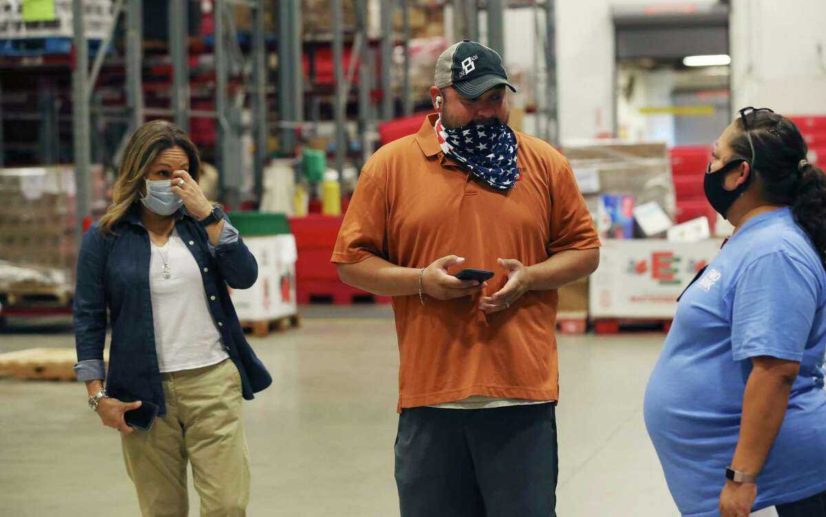 CRE8AD8 owner Gregorio Palomino, left, talks with San Antonio Food Bank Produce Procurement Manager Dayna Robokowski after he delivered five pallets of food boxes.