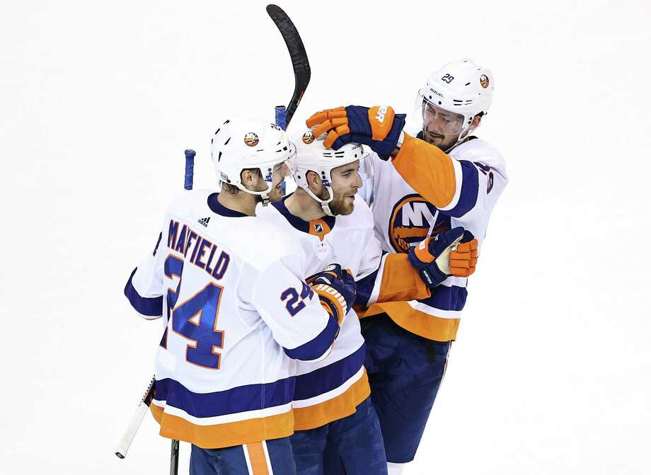Former Quinnipiac defenseman Devon Toews is congratulated by New York Islanders' teammates Scott Mayfield and Brock Nelson after scoring an empty-net goal against the Philadelphia Flyers on Monday night. Photo: Elsa / Getty Images / 2020 Getty Images