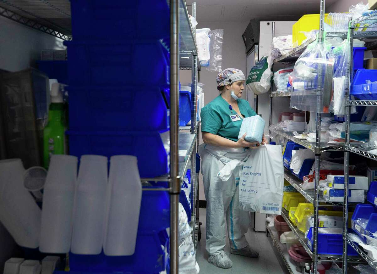 Nurse Christina Mathers loads up supplies in a plastic bag before heading into the negative pressure section of the ICU, to check on her patients at United Memorial Medical Center on Wednesday, July 22, 2020, in Houston. UMMC's chief medical officer, Dr. Joseph Varon, said that the hospital has stockpiled personal protective equipment and prepared its staff for Hurricane Laura.