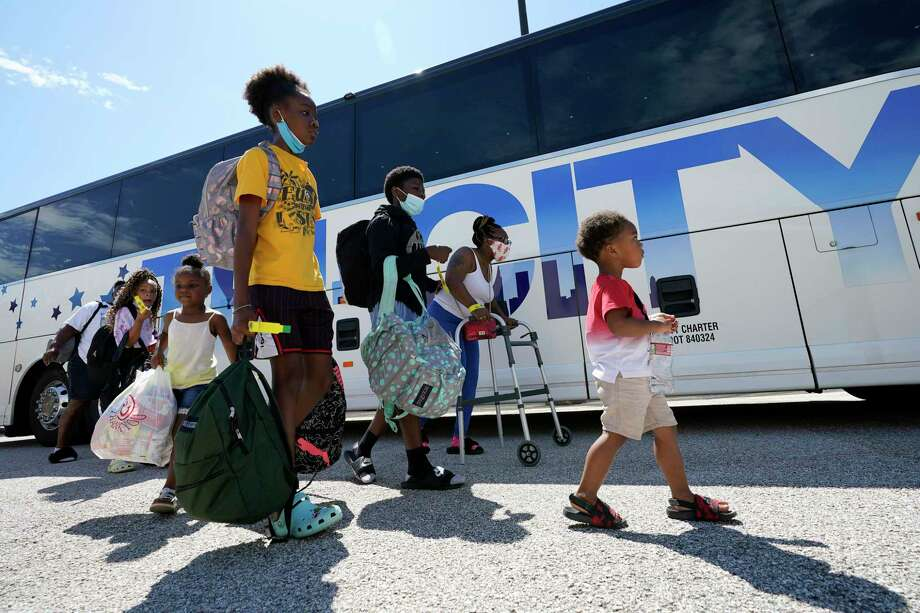 Evacuees walk to board buses Tuesday, Aug. 25, 2020, in Galveston, Texas. The evacuees are being taken to Austin, Texas, as Hurricane Laura heads toward the Gulf Coast. (AP Photo/David J. Phillip) Photo: David J. Phillip, STF / Associated Press / Copyright 2020 The Associated Press. All rights reserved.