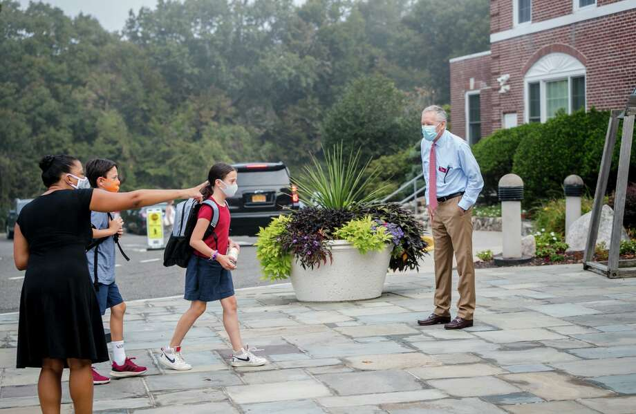 SLS Head of Middle School Amber Berry and Head of School Mark Davis, both New Canaan residents greeting and guiding studentson the first day of school on Monday. Reopening the campus comes with some modifications to ensure everyone's safety and health. Before arriving each day, students must complete an online wellness check. Once on the Hilltop, they must wear properly fitting masks and use one of the new portable hand-washing stations before entering the building. Inside, desks are spaced apart, partitions separate seats at the lunch tables, and signs remind us all to stay socially distant.  Photo: Keyz 2 Life Media / @ St. Luke's School