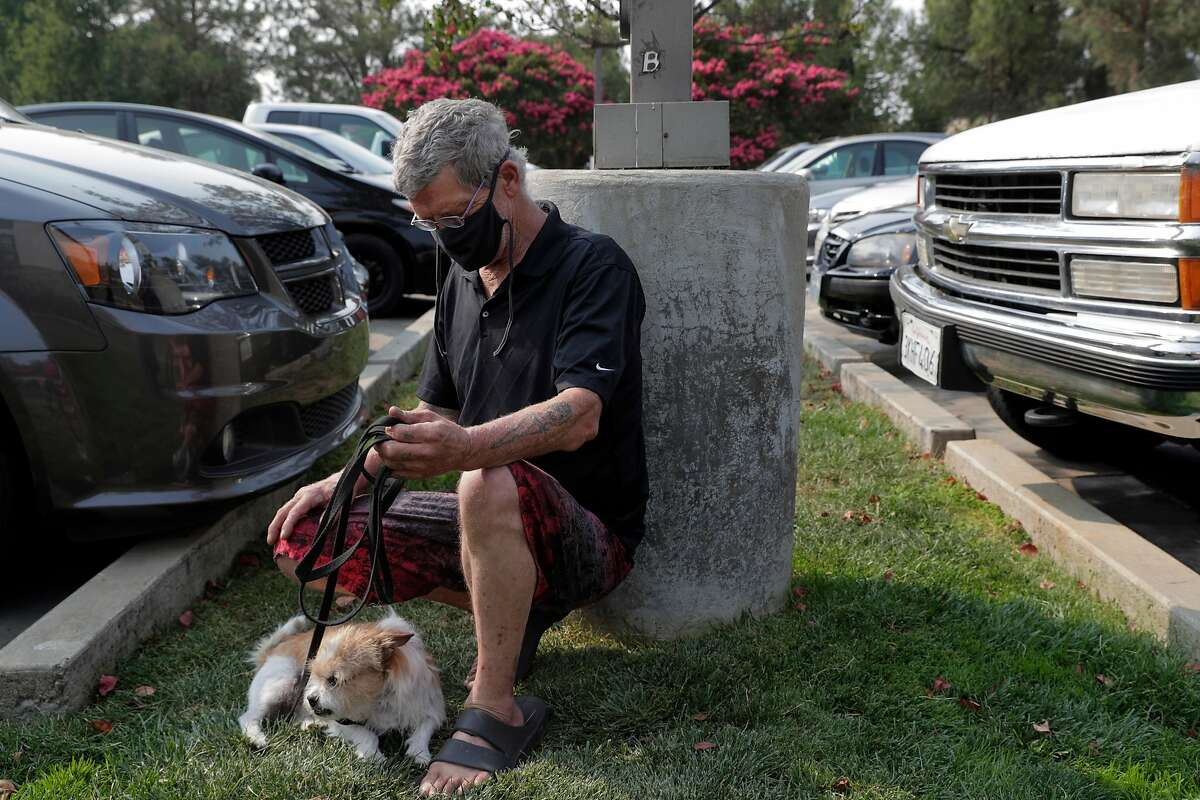 David Mackert plays with is dog Astro at the Extended Stay America where he evacuated as the local fires continued to keep people from returning to their home in Fairfield, Calif., on Monday, August 24, 2020.