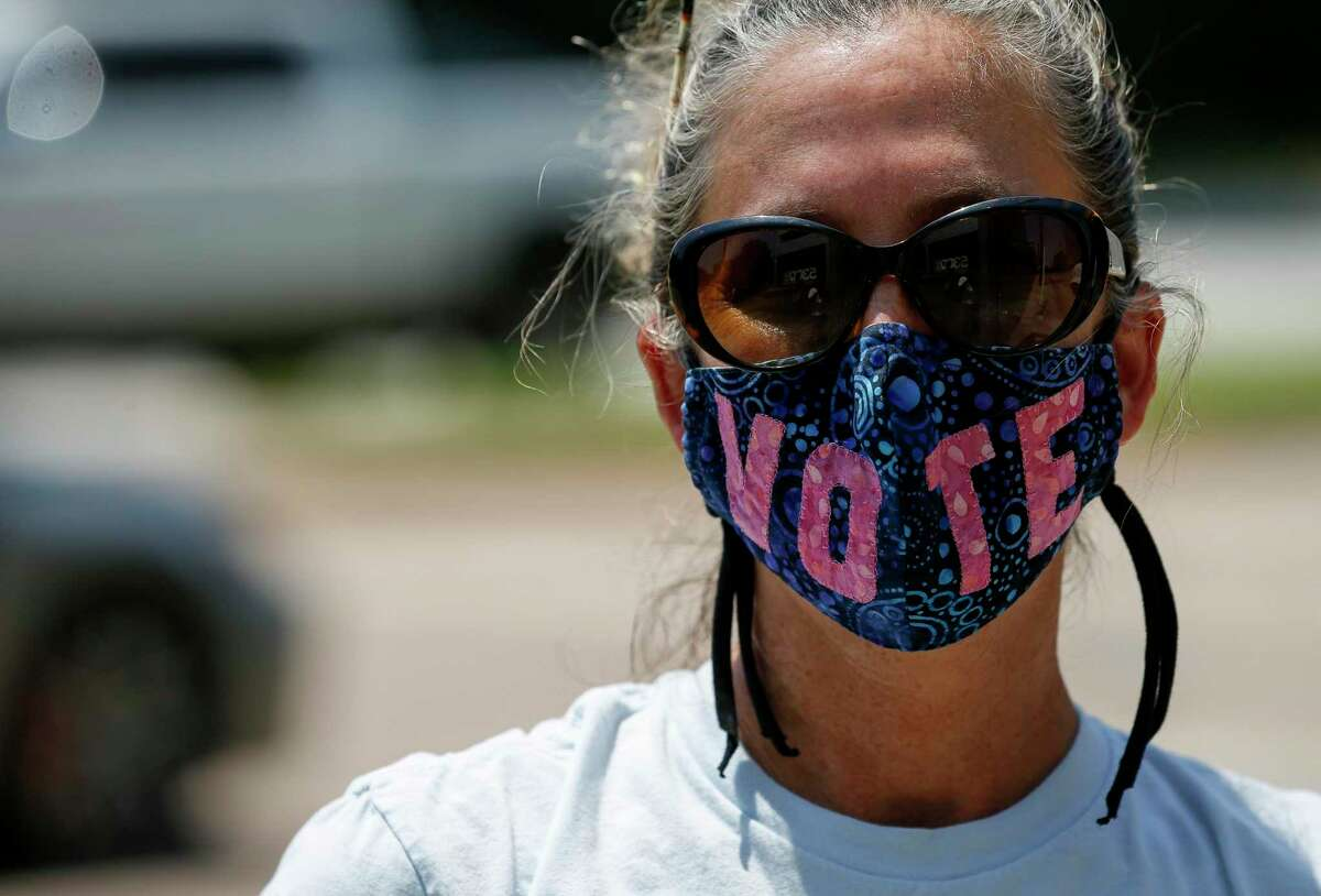 """Laurel Hays wears a face mask which reads """"Vote"""" during a protest outside Senator John Cornyn's office Tuesday, Aug. 18, 2020, in Houston."""