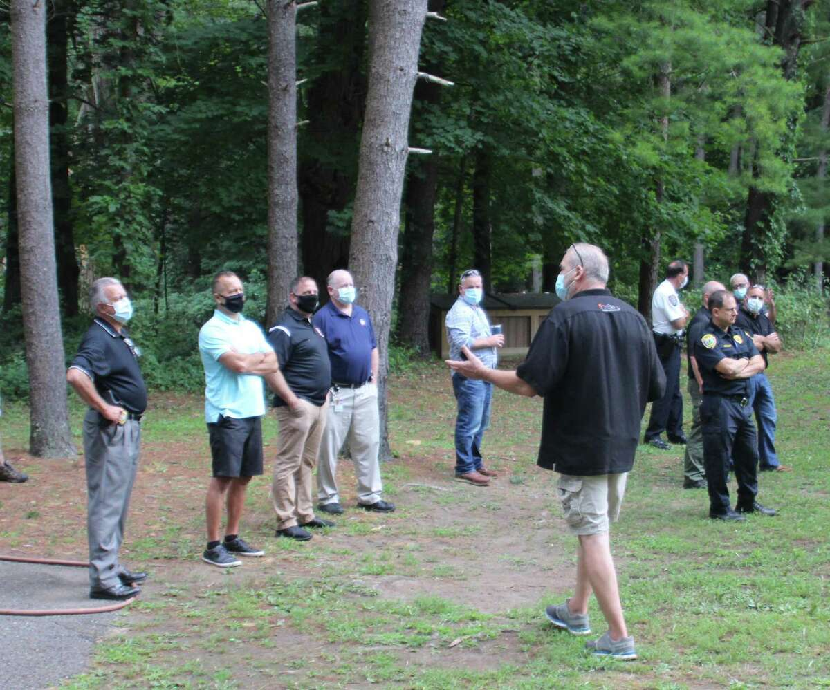 A group of attendees, including many first responders, listens as some of the features of a drone are explained.