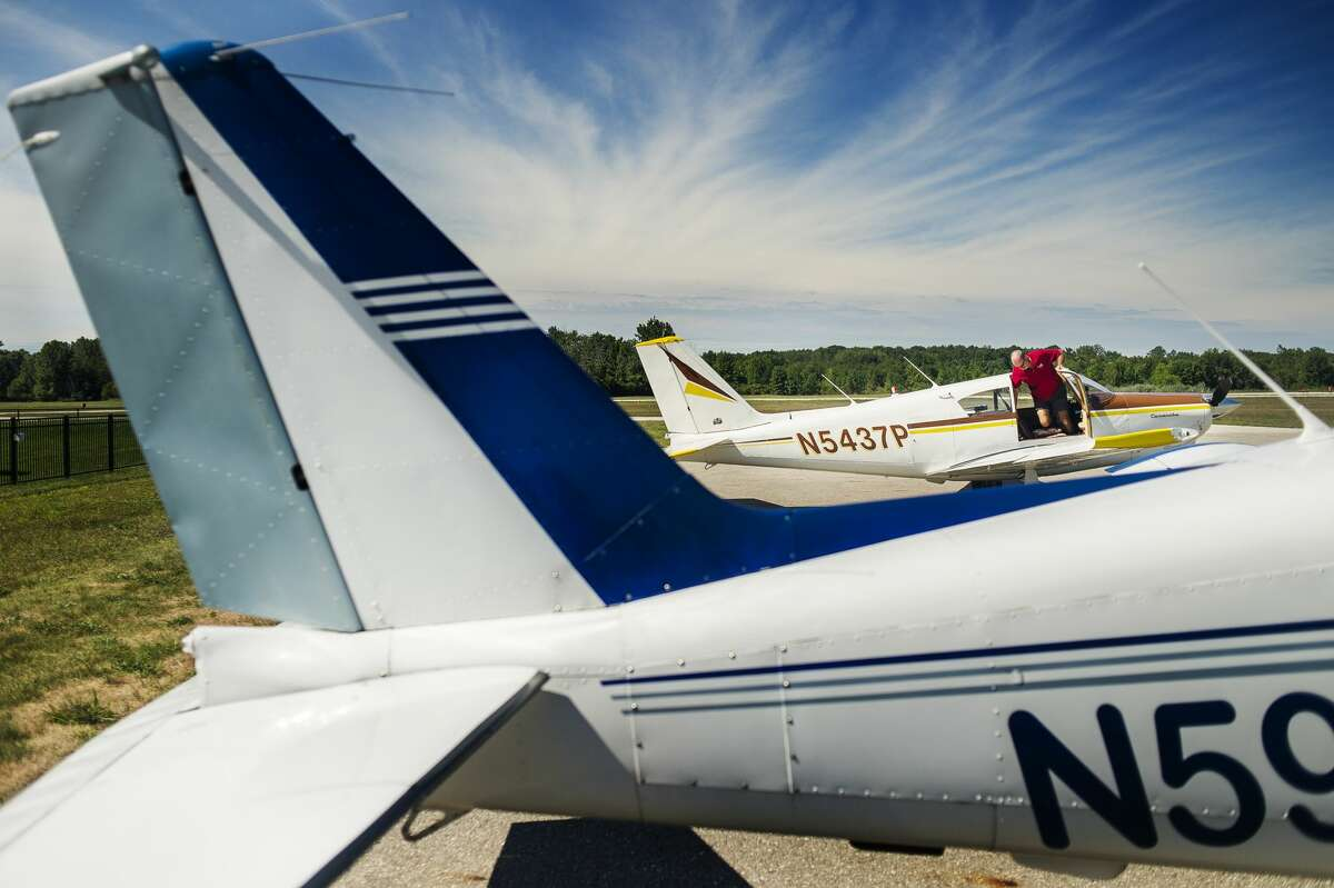 Jeff Westin hops down from his airplane before sitting down for lunch with friends Tuesday, Aug. 25, 2020 at Jack Barstow Airport. The three couples flew into Midland from the Home Acres Sky Ranch Airport in Lake City in their separate airplanes to share a meal. (File/Midland Daily News)