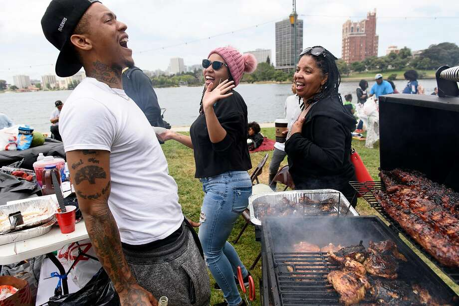 "Michael Woods, left, dances with his sister Clarice Brown and their mother Michelle Beasley while tending to his grill  during the ""BBQ'n While Black"" party at Lake Merritt in Oakland, CA, on Sunday May 20, 2018. Photo: Michael Short / Special To The Chronicle"