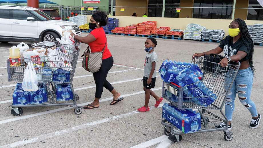 Kendriah Williams, Kevin Williams, 7, and Quin Cook picked up the maximum number of cases of water at HEB Plus on Dowlen Road just in case. With two storms churning in the Gulf of Mexico, folks in Southeast Texas were out picking up what they may need if the bad weather hits the area. Photo made on August 22, 2020. Fran Ruchalski/The Enterprise Photo: Fran Ruchalski, The Enterprise / The Enterprise / © 2020 The Beaumont Enterprise