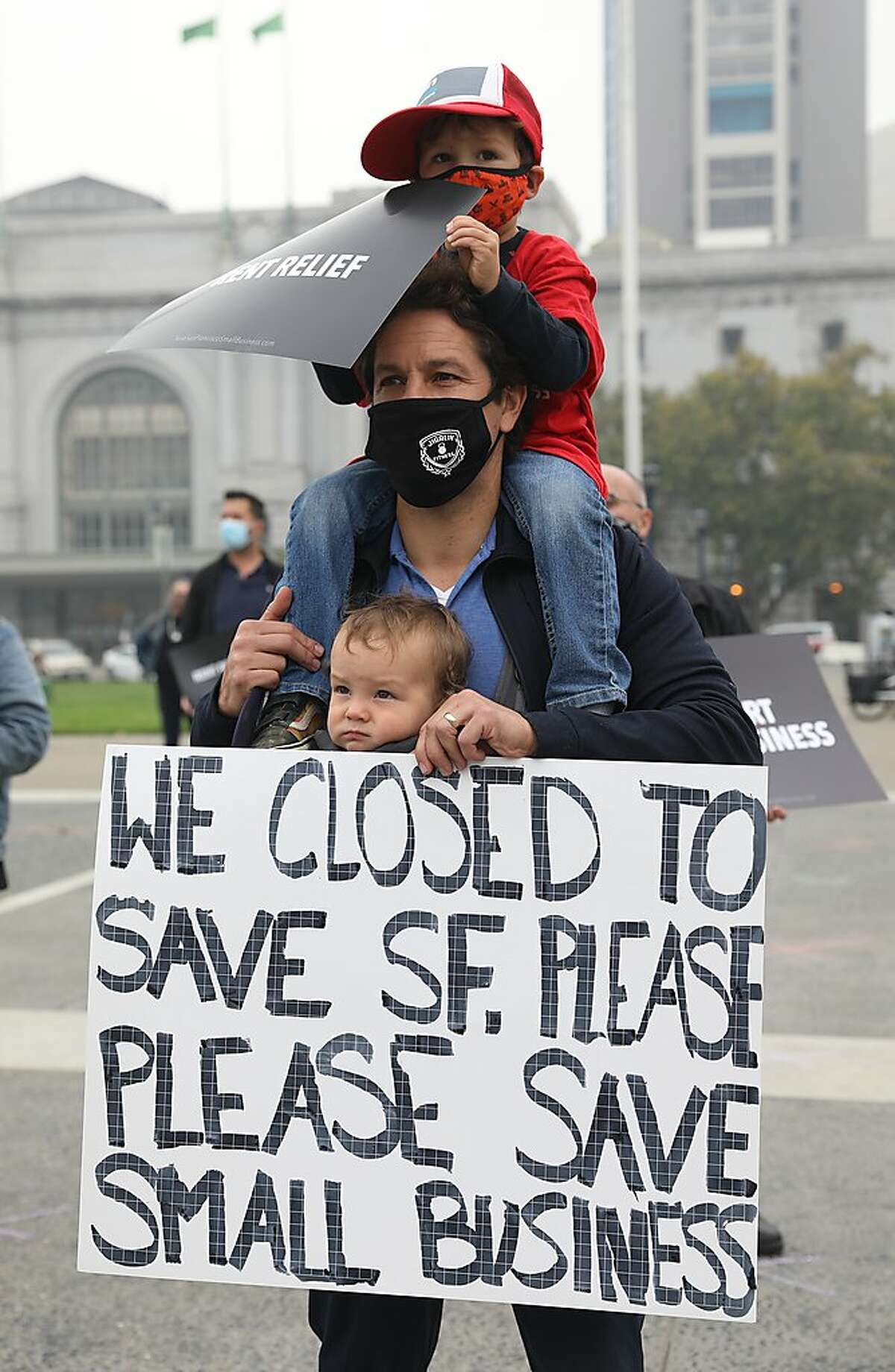 Michael Jigalin with his children Dominic, 1, and Nicolai, 4, protest at the plaza across from city hall on Tuesday, Aug. 25, 2020, in San Francisco, Calif.