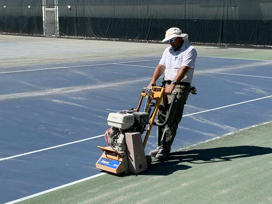 Workers from Three Rivers Corporation grind down the old surfaces of the Greater Midland Tennis Center's east outdoor courts on Tuesday in preparation for repairing and resurfacing them. Photo: Fred Kelly/fred.kelly@mdn.net