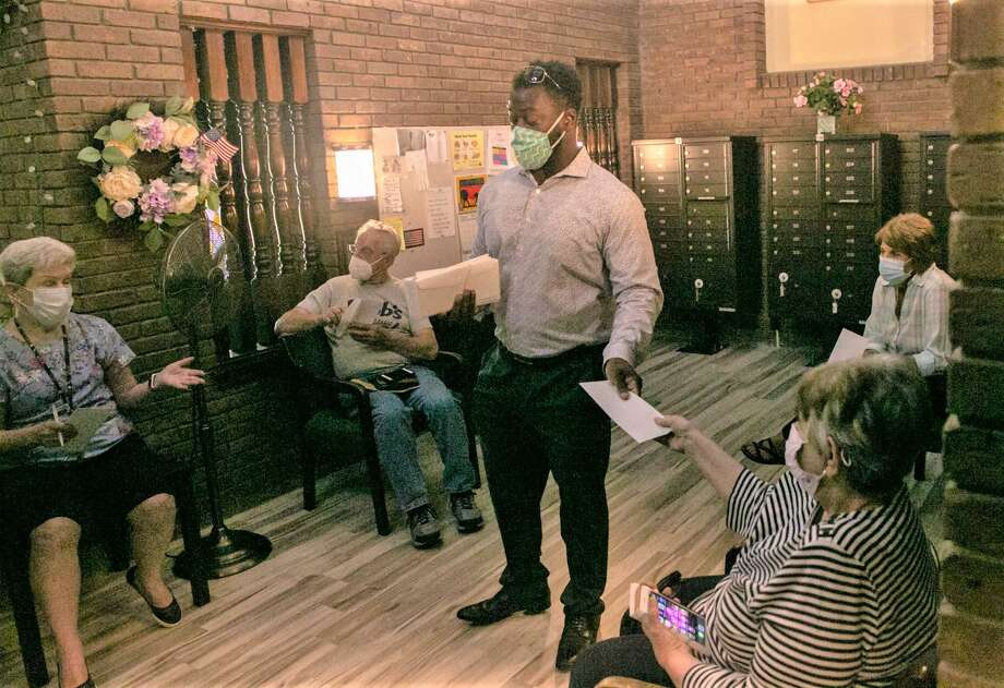 At center, state Rep. Quentin Phipps, D-Middletown, spoke last week to residents of Stonegate Apartments after the property owner issued non-renewal notices to more than a dozen tenants in the 55-and-older  community. Photo: Photos Courtesy Senate / House Democrats