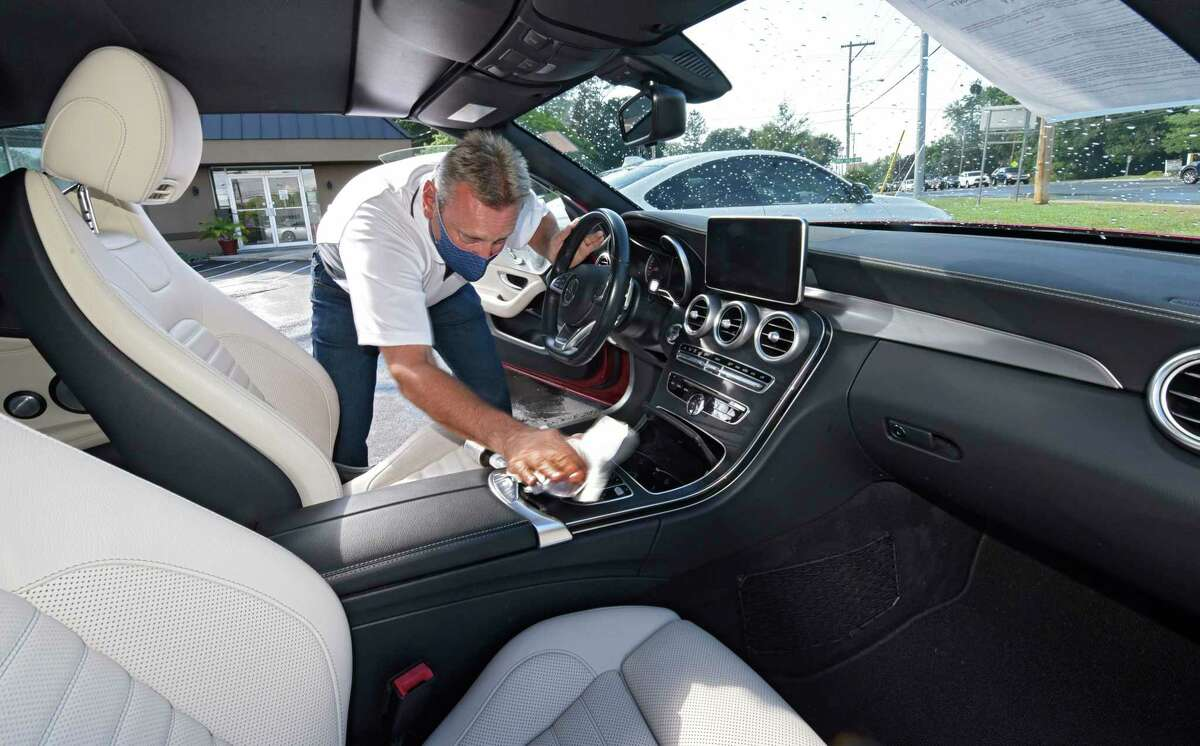 Bul AutoSale employee Dave Leonardo disinfects a car after a customer sat in the driver's seat on Tuesday, Aug. 25, 2020 in Colonie, N.Y. (Lori Van Buren/Times Union)