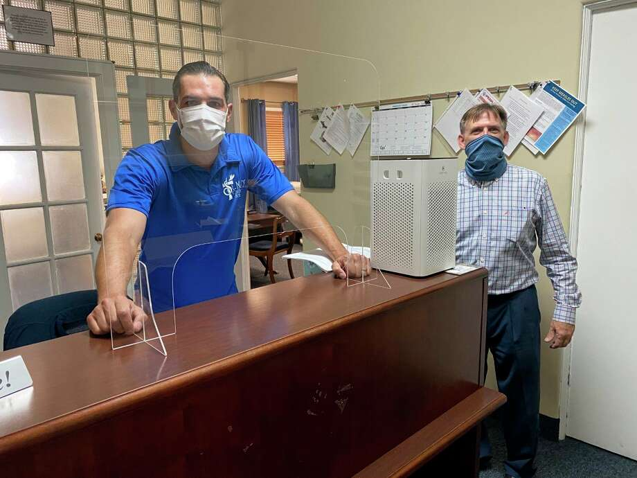 Pictured are Schuberg Insurance Agency owner Tyler Schuberg, left, and St. Mary Catholic School principal JB Watters with a new plexiglass desk divider. Dividers, along with 200 masks and air purifiers for each classroom were donated to the school by the insurance agency. (Courtesy photo)