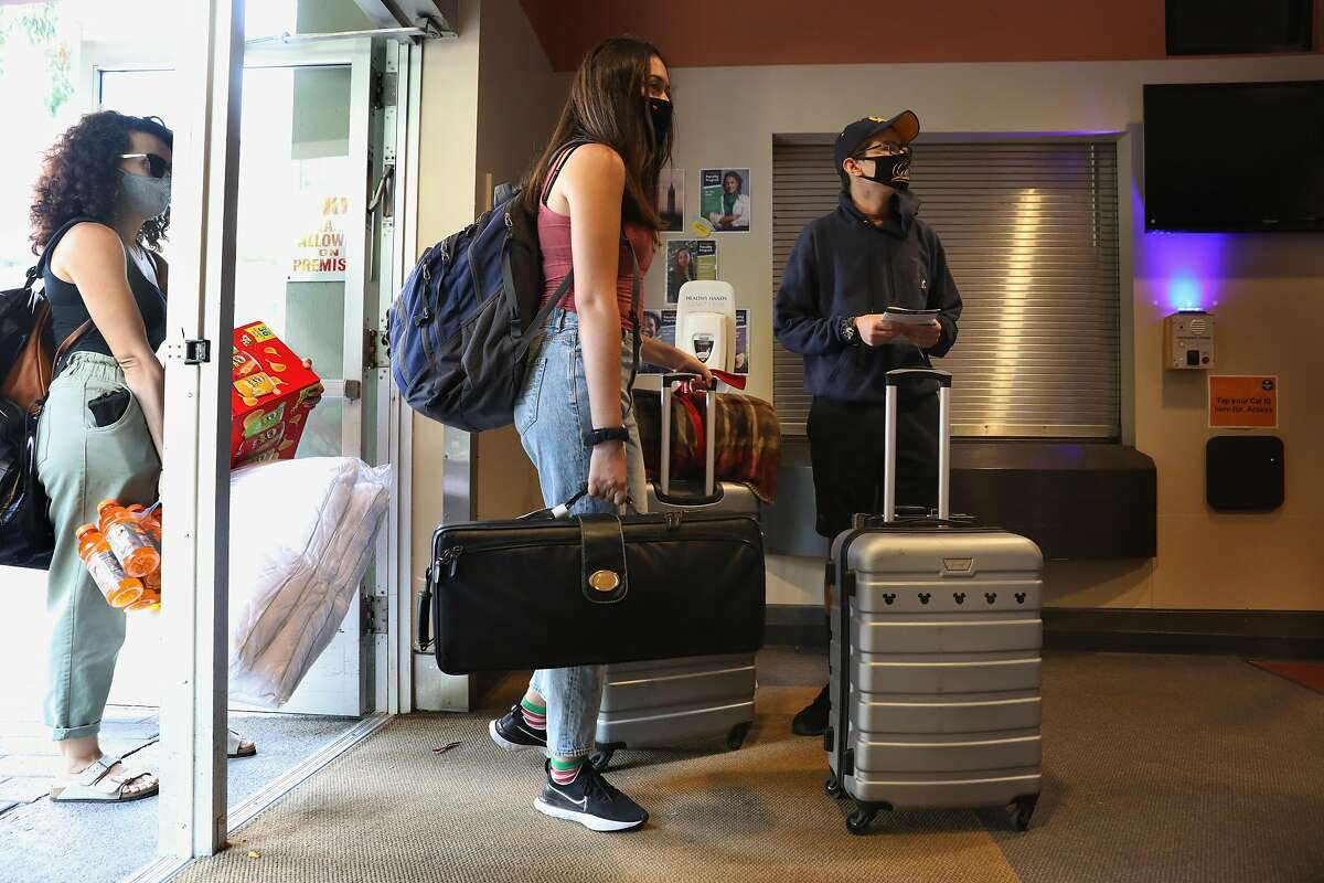 Student Sebastian Arevalo (right), 17 years old, from Southern California waits for the elevator to move into his dorm on Haste St. as family (left) help him move in his belongings on Thursday, Aug. 20, 2020, in Berkeley, Calif. Some of the 2,200 students who will be on campus will begin moving into Units 1 and Units 2 next to the UC Berkeley campus.