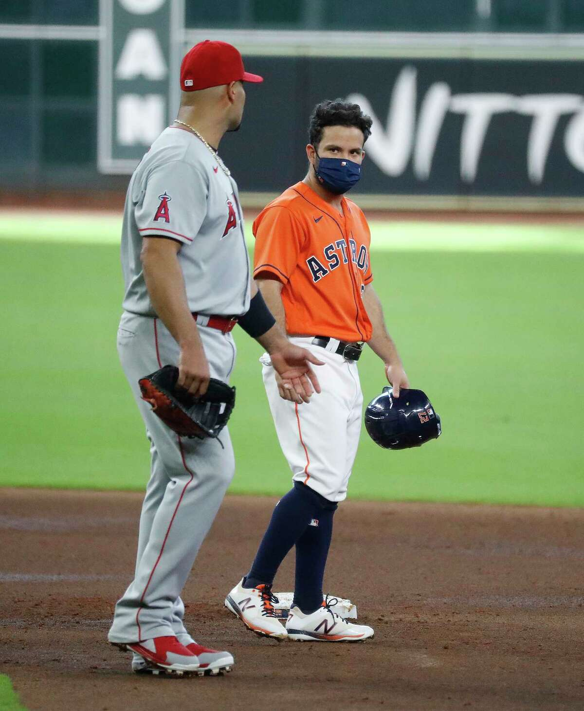 Houston Astros Jose Altuve (27) and Los Angeles Angels first baseman Albert Pujols (5) chat during a pitching change during the second inning of an MLB baseball game at Minute Maid Park, Tuesday, August 25, 2020, in Houston.