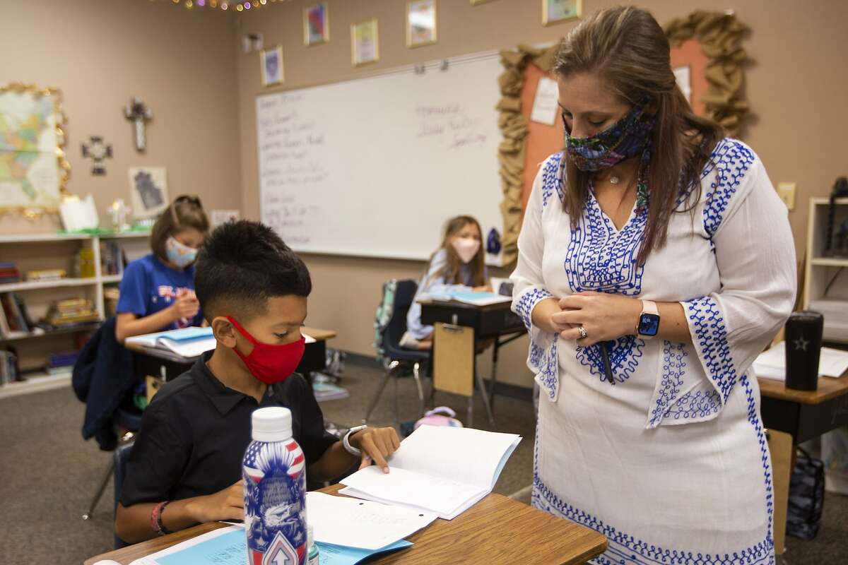 Fifth-grade teacher Amanda Cardona talks with 9-year-old Ray Urias about the assignment Tuesday morning, Aug. 25, 2020, in her classroom at St. John's Episcopal School in Odessa Texas. Classes at St. John Episcopal School resumed with a limited classroom student size of 12. (Ben Powell/Odessa American via AP)