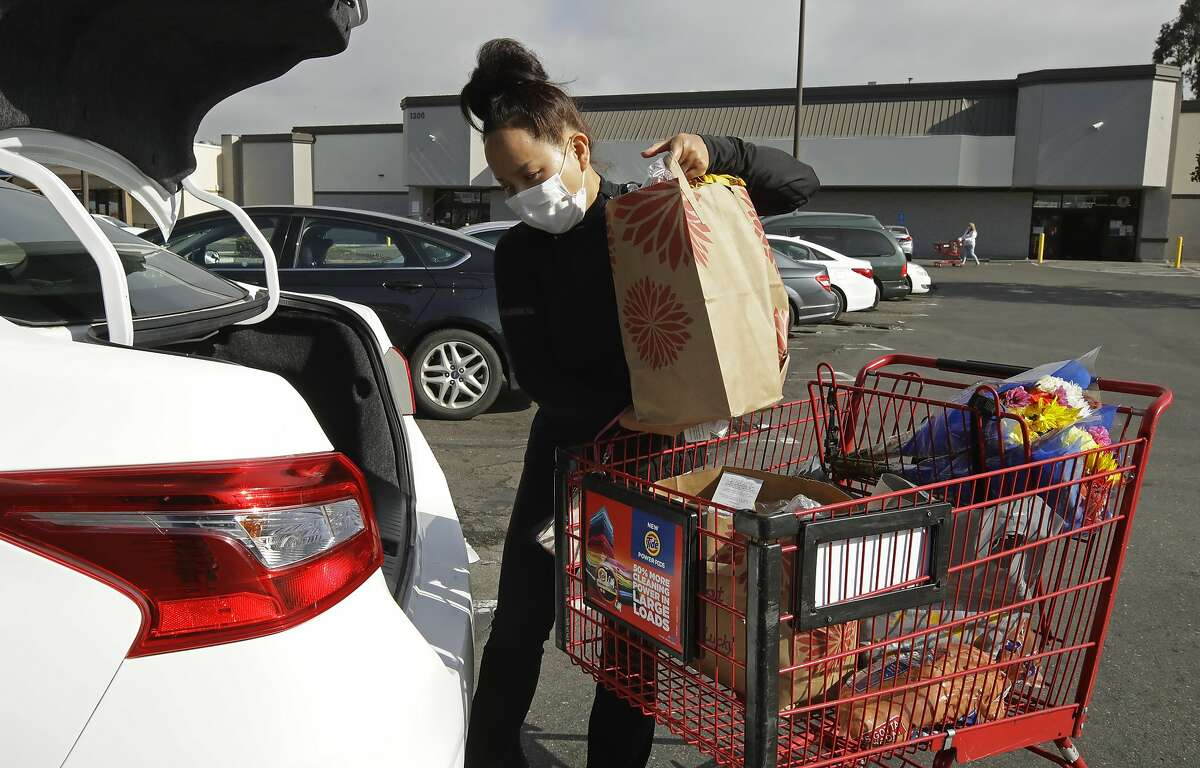 Advocates say contractors such as Instacart worker Saori Okawa, shown in San Leandro, should get higher priority for receiving a COVID-19 vaccination.