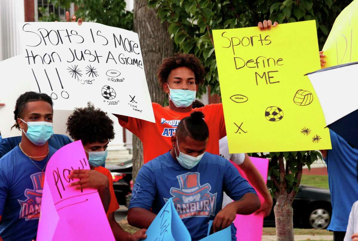 Danbury High School athlete Nick Smith holds up signs during a protest against the cancellation of high school sports after a COVID-19 spike in the city at Danbury City Hall in Danbury, Conn., on Tuesday Aug. 25, 2020.