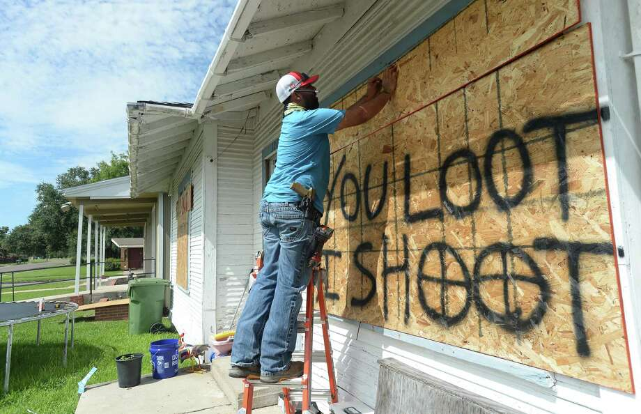 """Jose Zepeda boards up his home in Port Arthur and painted a warning to looters as evacuations begin Tuesday in Port Arthur.Zepeda says his wife and children had already left, but he is staying to ensure the safety of their home. """"I work for the plants, and I also have a side business and have a lot of tools. I worked hard for all of that, and I'm not going to let someone take it."""" Zepeda has a generator to help maintain power, """" and I have plenty of fuel, food, drinks, and bullets."""" Photo taken Tuesday, August 54, 2020 Kim Brent/The Enterprise Photo: Kim Brent / The Enterprise / BEN"""