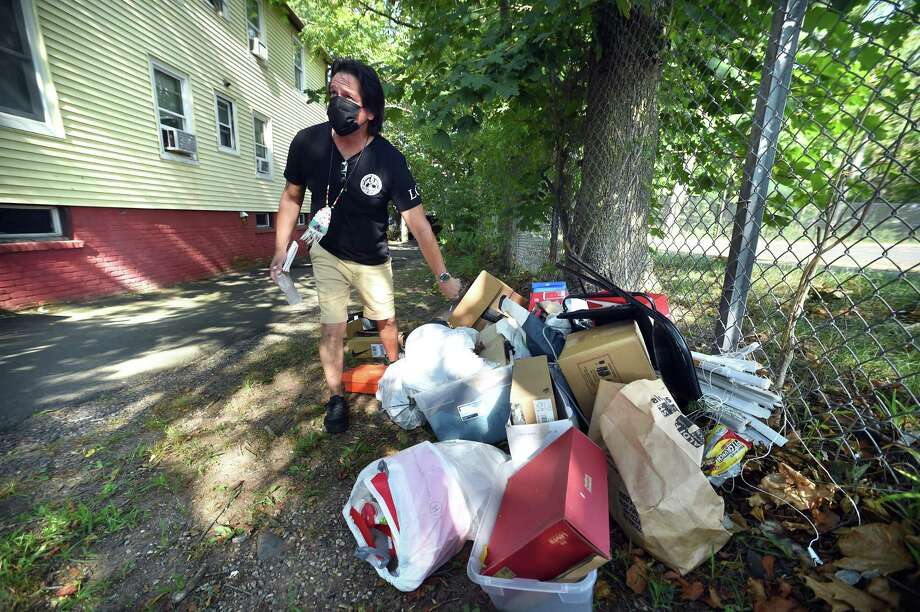 LCI Housing Code Enforcement Officer Rickie Mazzadra inspects garbage in the yard of a property on Farnham Avenue in New Haven on Tuesday. Photo: Arnold Gold / Hearst Connecticut Media / New Haven Register