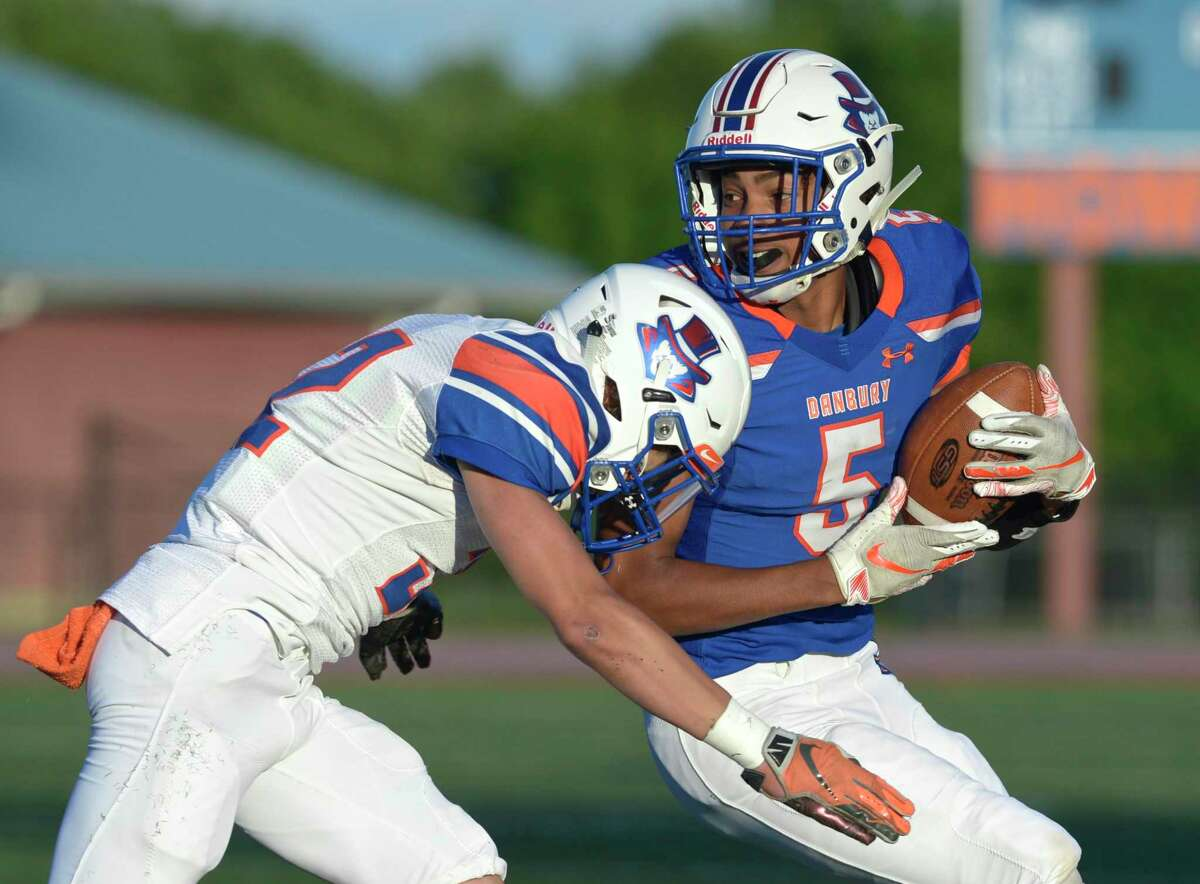 Nick Smith (5 Blue) is hit by Dylan Joyner (32 White) after catching a pass in the Danbury High School Hatters Blue & White spring football game. Friday, June 14, 2019, at Danbury High School, Danbury, Conn.