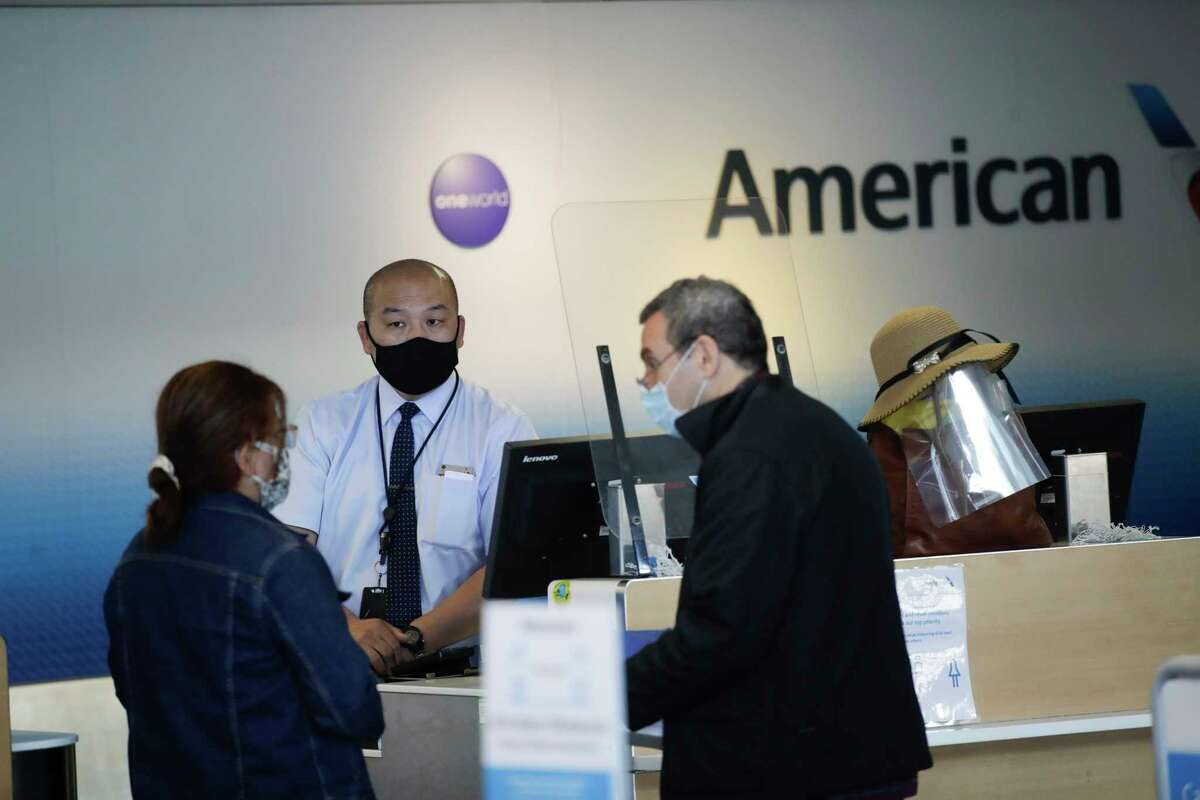 FILE - In this May 28, 2020 file photo, travelers check in at the American Airlines terminal at the Los Angeles International Airport in Los Angeles. American Airlines says it will furlough or lay off 19,000 employees in October as it struggles with a sharp downturn in travel because of the pandemic. (AP Photo/Marcio Jose Sanchez, File )