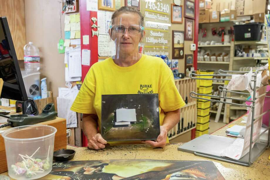 Jo Burke of Burke Hardware in Deweyville stands at the counter with a picture of their store after floodwaters devastated the area in 2016. She's hoping they'll do OK in the coming hurricane and be able to continue serving their neighbors in the community when it's over. The largely rural, pine-canopied communities of Jasper and Newton counties find themselves facing a threat more common to coastal communities Photo made on August 25, 2020. Fran Ruchalski/The Enterprise Photo: Fran Ruchalski, The Enterprise / The Enterprise / © 2020 The Beaumont Enterprise