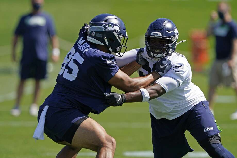 Alton Robinson (right), a fifth-round pick out of Syracuse, has been one of the most talked about Seahawks rookies early in training camp practices. He's emerged as a candidate to be an immediate contributor for Seattle's pass rush in 2020. Photo: Ted S. Warren/AP / Copyright 2020 The Associated Press. All rights reserved.
