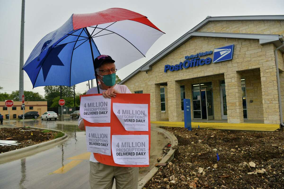 Tom Sullivan stands in the rain as residents gathered outside the Alamo Heights Post Office while participating in a national call for action to prevent President Donald Trump and Senate republicans for sabotaging voting by mail for the 2020 general election.