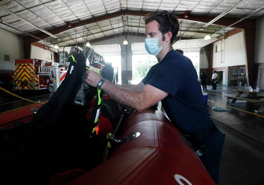 Porter firefighter Seth Arnold checks a life vests from a rescue boat as firefighters prepare equipment ahead of Hurricane Laura, Tuesday, Aug. 25, 2020, in Porter. Photo: Jason Fochtman, Houston Chronicle / Staff Photographer / 2020 © Houston Chronicle
