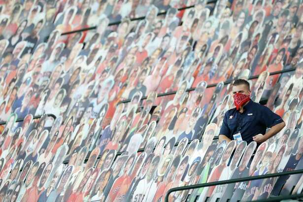A Houston Astros employee sits among the fan cutouts looking for foul balls during the first inning of the second game in a double header during an MLB baseball game at Minute Maid Park, Tuesday, August 25, 2020, in Houston.