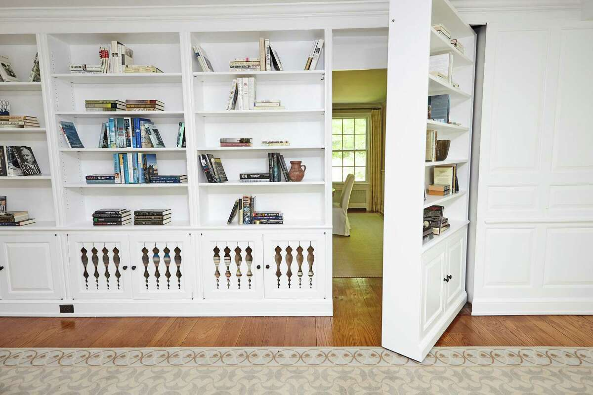 The family room features built-in shelving and a surprising section of the shelving that opens like a door into the dining room.