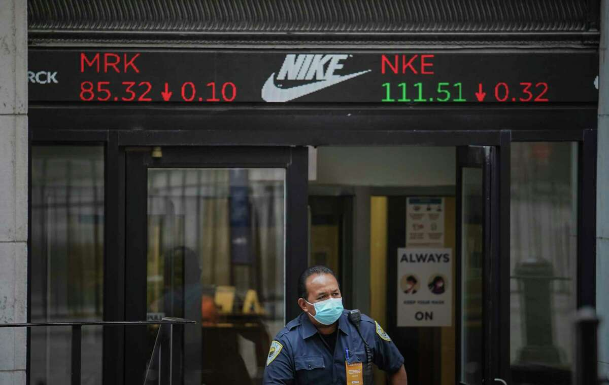 A security agent exits the New York Stock Exchange building as a ticker above the doorway carries the latest trading information, Tuesday Aug. 25, 2020, in New York. U.S. stocks are drifting close to their record heights Tuesday, as momentum slows on Wall Street. (AP Photo/Bebeto Matthews)