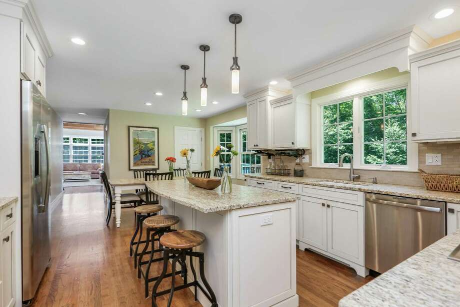 In the sizable remodeled kitchen there are Grabill high-end custom kitchen cabinets, granite counters and a center island with a breakfast bar for three.