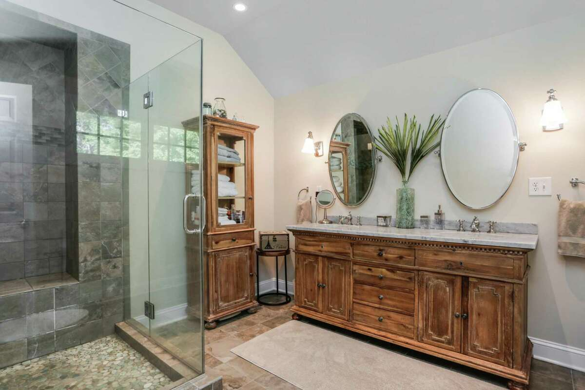 The master bath has a double vanity and glass shower.