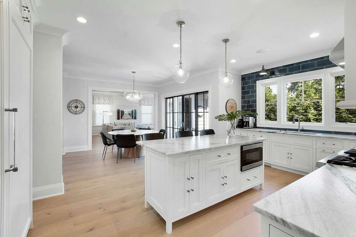 High-end appliances include a double size Sub-Zero refrigerator/freezer and a Thermador range with a pot-filler, and the eat-in area has sliding doors to the yard.