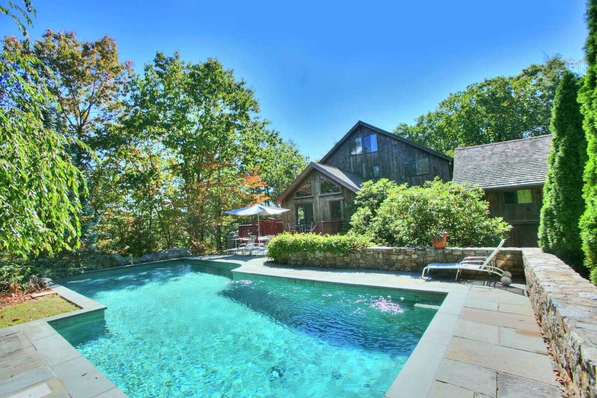 Nestled into this two-acre property is a heated Gunite in-ground swimming pool with a waterfall feature and a fieldstone sitting wall.