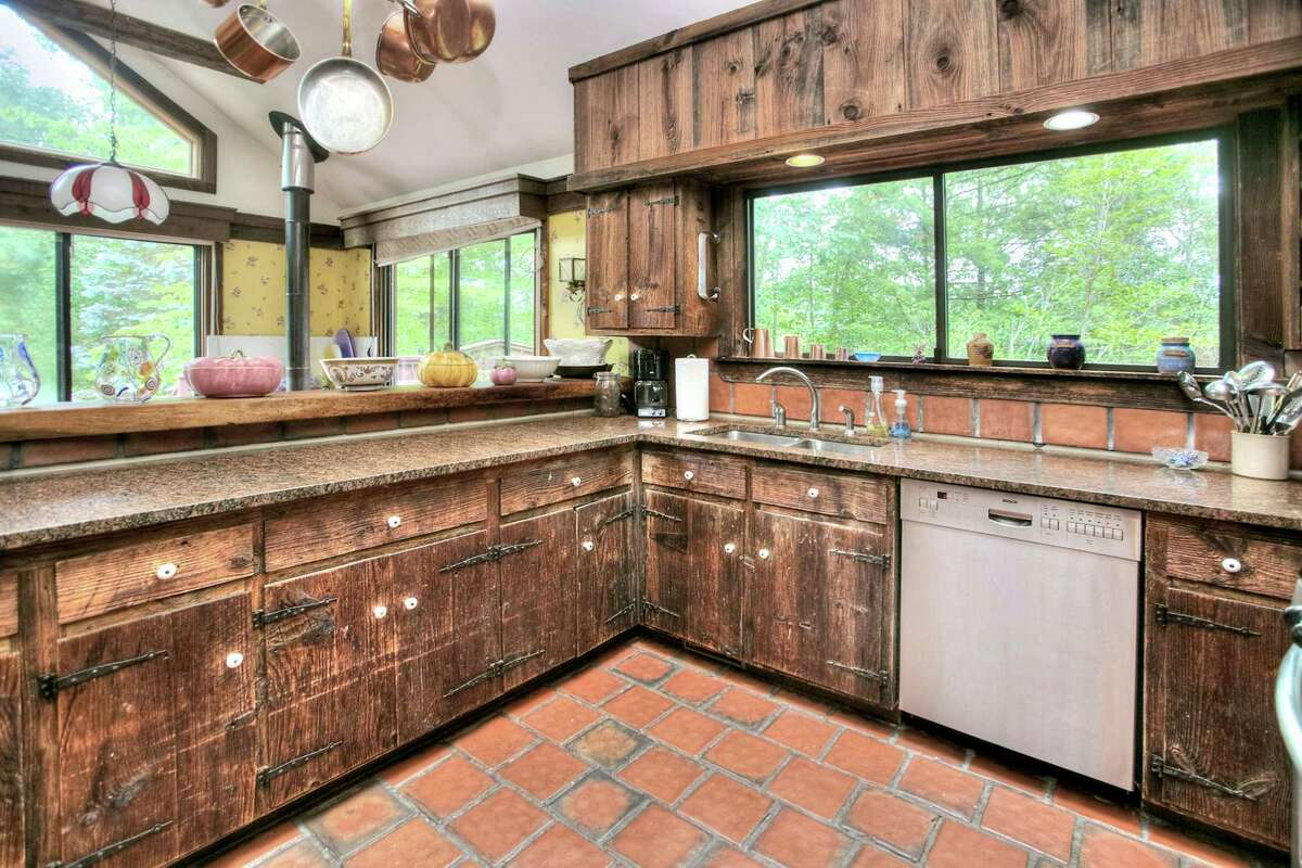 In the rustic kitchen there is a vaulted ceiling, granite counters, reclaimed wood cabinetry and ceramic tile floor.