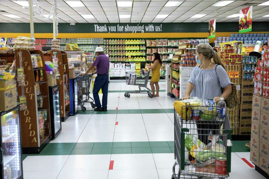 Customers wear masks at a grocery store in Altamonte Springs, Fla., July 17, 2020. More than six million people enrolled in food stamps in the first three months of the coronavirus pandemic, an unprecedented expansion that is likely to continue as more jobless people deplete their savings and billions in unemployment aid expires this month. (Charlotte Kesl/The New York Times) Photo: CHARLOTTE KESL, STR / NYT / NYTNS