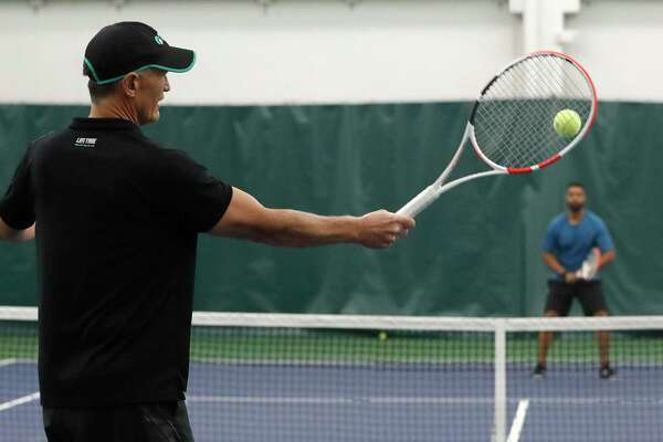 Life Time Galleria Tennis manager, Gary Armstrong returns to Richard Creavalle at Life Time Galleria Tennis, Wednesday, August 19, 2020, in Houston. Interest in tennis is on the upswing in Houston, and tennis has been ranked as one of the safest sports people can play during the pandemic, due to its natural social distancing.