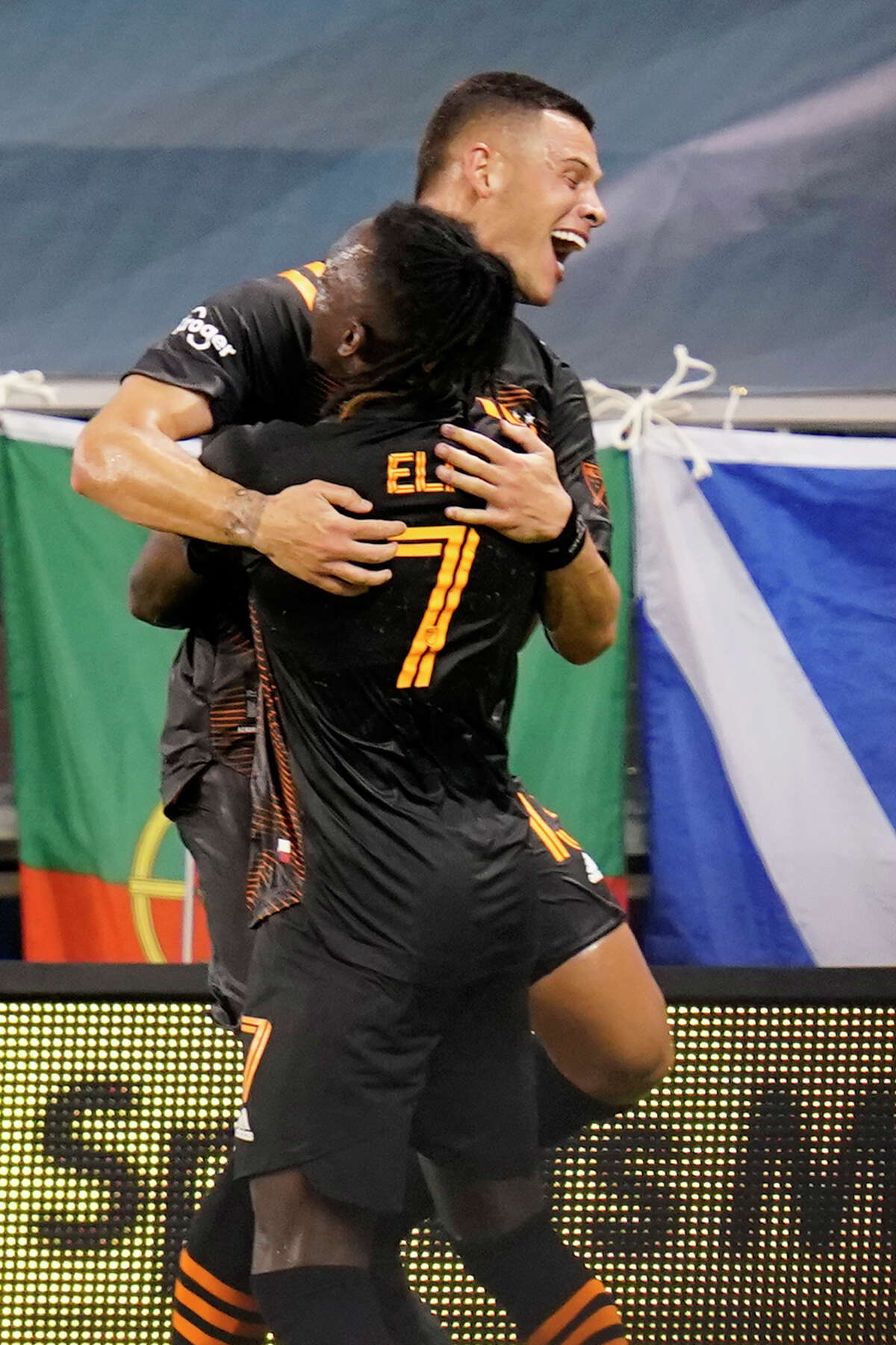 Houston Dynamo forward Christian Ramirez, back, celebrate his goal with teammate Alberth Elis (7) during the first half of an MLS soccer match against Sporting Kansas City in Kansas City, Kan., Tuesday, Aug. 25, 2020. (AP Photo/Orlin Wagner)