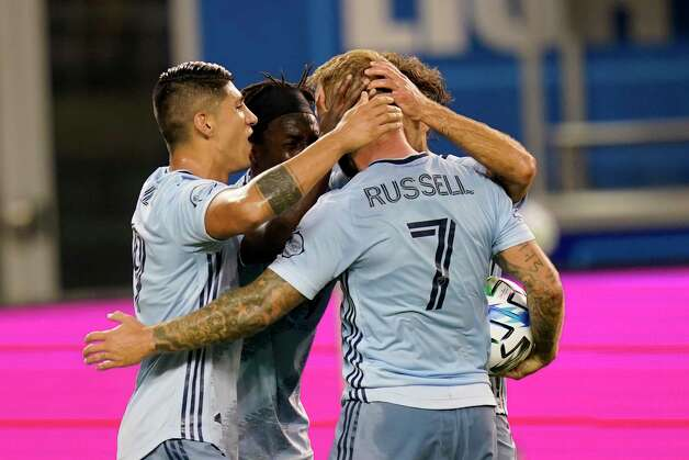 Sporting Kansas City forward Johnny Russell (7) is congratulated by teammates after scoring a goal during the first half of an MLS soccer match against the Houston Dynamo in Kansas City, Kan., Tuesday, Aug. 25, 2020. (AP Photo/Orlin Wagner) Photo: Orlin Wagner, Associated Press / Copyright 2020 The Associated Press. All rights reserved