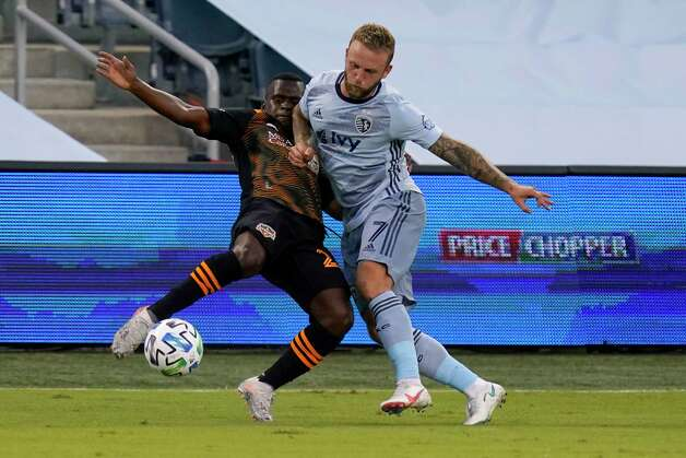 Houston Dynamo forward Carlos Darwin Quintero, left, plays the ball against Sporting Kansas City forward Johnny Russell (7) during the first half of an MLS soccer match in Kansas City, Kan., Tuesday, Aug. 25, 2020. (AP Photo/Orlin Wagner) Photo: Orlin Wagner, Associated Press / Copyright 2020 The Associated Press. All rights reserved