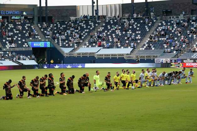 Teams kneel during the national anthem before an MLS soccer match between Sporting Kansas City and the Houston Dynamo in Kansas City, Kan., Tuesday, Aug. 25, 2020. (AP Photo/Orlin Wagner) Photo: Orlin Wagner, Associated Press / Copyright 2020 The Associated Press. All rights reserved
