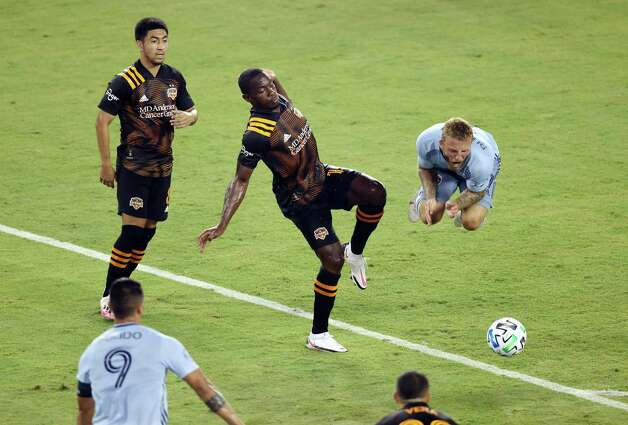 KANSAS CITY, KANSAS - AUGUST 25:  Johnny Russell #7 of Sporting Kansas City is upended by Maynor Figueroa #15 of Houston Dynamo during the game at Children's Mercy Park on August 25, 2020 in Kansas City, Kansas. Photo: Jamie Squire, Getty Images / 2020 Getty Images
