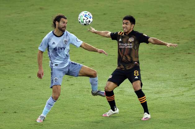 KANSAS CITY, KANSAS - AUGUST 25:  Graham Zusi #8 of Sporting Kansas City and Memo Rodriguez #8 of Houston Dynamo compete for the ball during the game at Children's Mercy Park on August 25, 2020 in Kansas City, Kansas. Photo: Jamie Squire, Getty Images / 2020 Getty Images