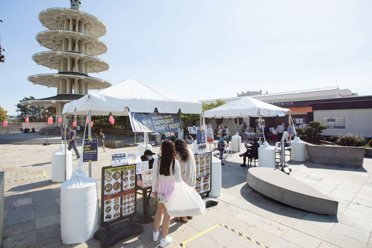 Customers order at restaurant booths in Japan Center's Peace Plaza on Aug. 21, 2020. Because the Japan Center malls have been closed to the public, restaurants inside are offering takeout services at tents set up on the center's plaza.