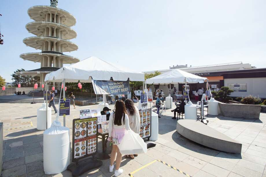 Customers order at restaurant booths in Japan Center's Peace Plaza on Aug. 21, 2020. Because the Japan Center malls have been closed to the public, restaurants inside are offering takeout services at tents set up on the center's plaza. Photo: Douglas Zimmerman/SFGATE / SFGATE